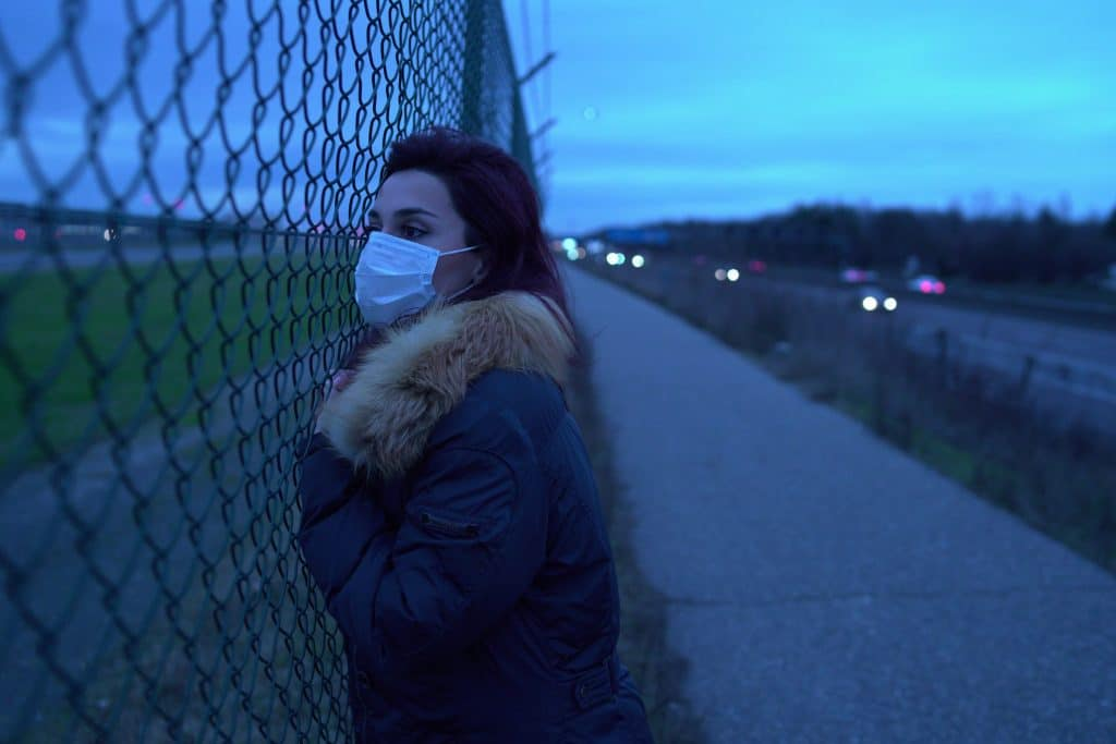 image of a woman wearing a surgical mask leaning on a chainlink fence looking longingly into the distance