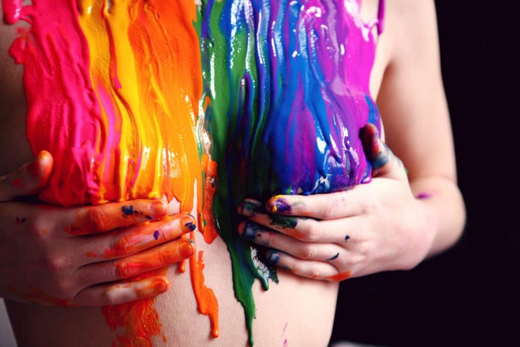 image of a woman's torso covered in the Gay Pride rainbow paint colors